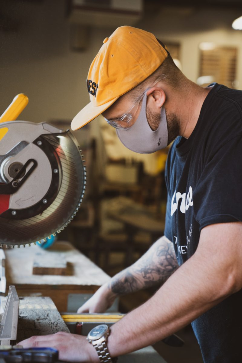 Photo of a man working with a bandsaw.