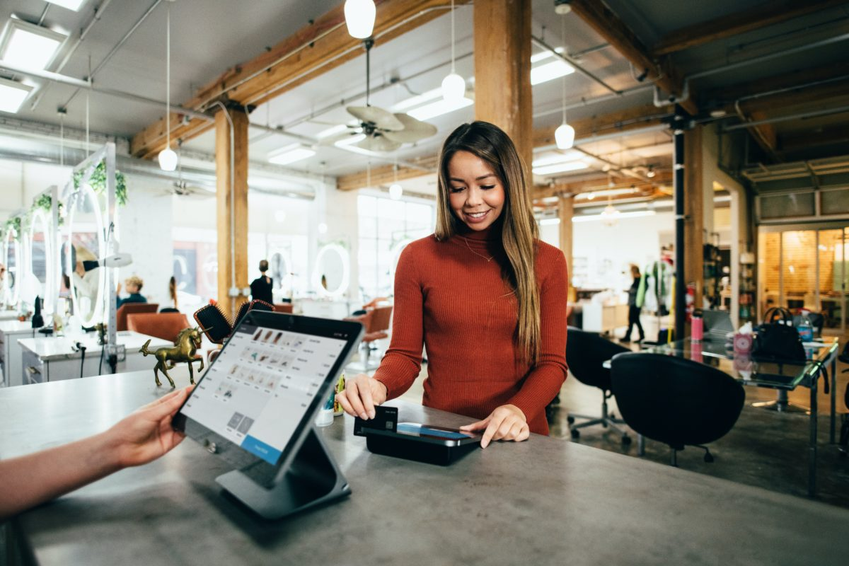 Woman paying at a cashier with a credit card