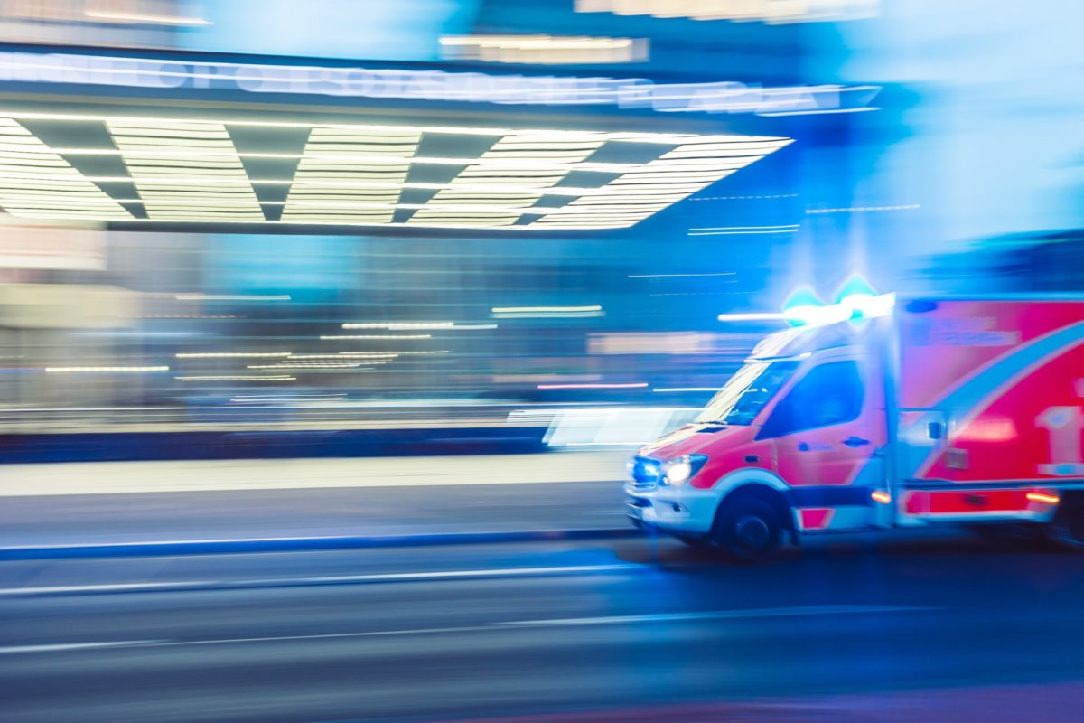 Photo of an ambulance with lights on in motion.