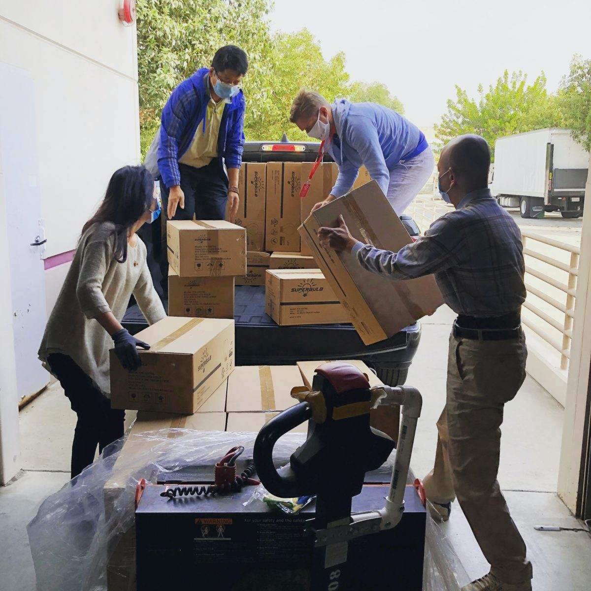 A group of volunteers loading boxes into a pickup truck.