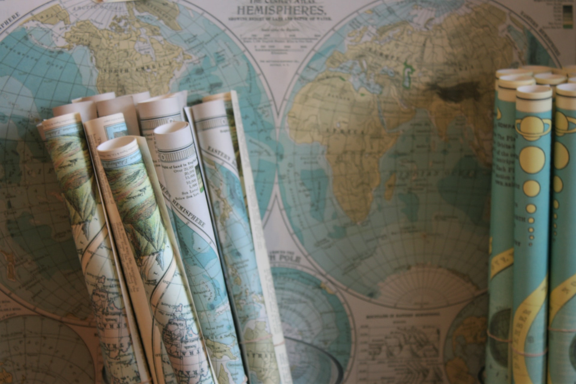Rolls of maps in front of a map on a wall