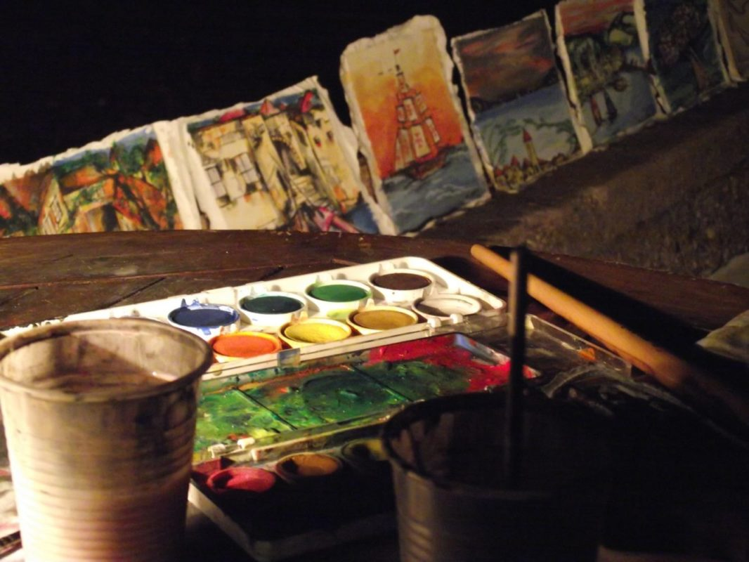 A palette of watercolors on the table and paintings drying in the background