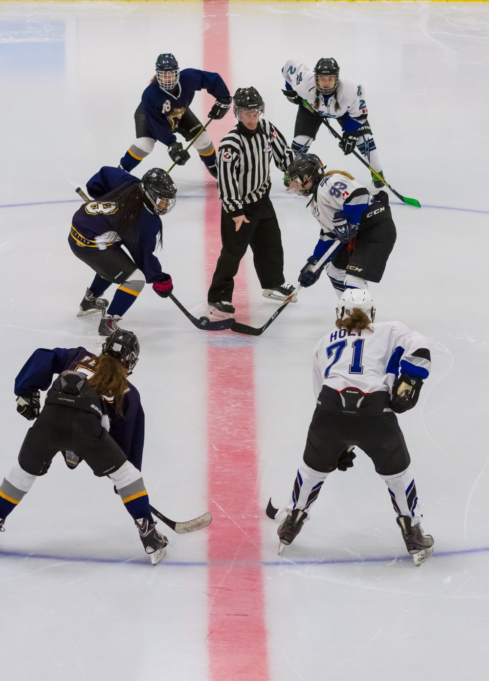 Two women's' ice hockey teams line up at the faceoff circle