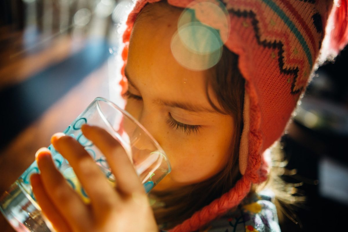 A young girl drinking water from a glass.