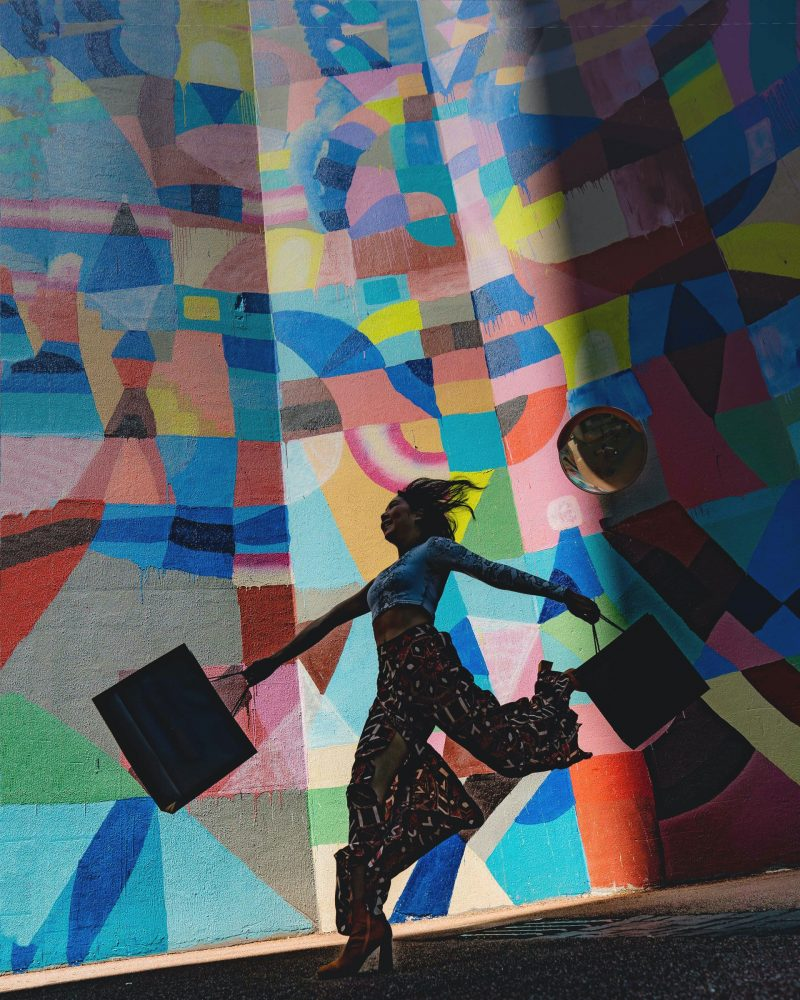 Woman carrying bags jumping for joy in front of a colorful mural