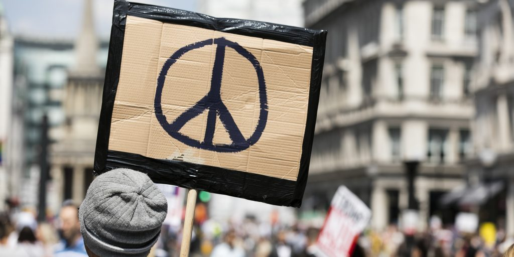 A person holds a peace sign banner at a protest