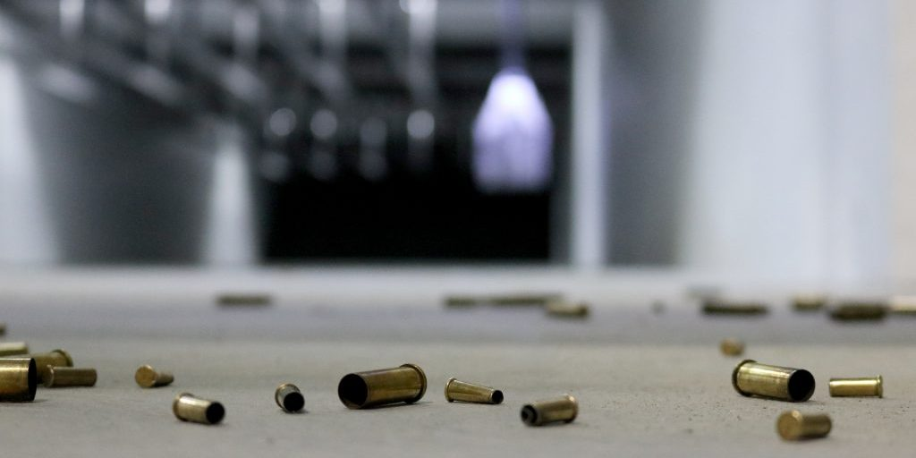 A variety of different shell casings spread across the floor at a shooting range with target in the background.