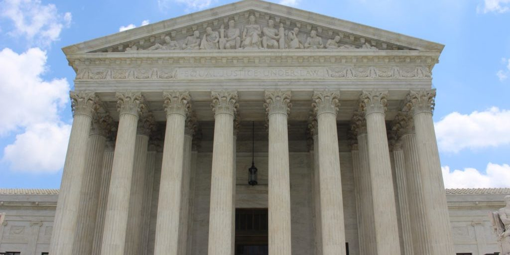 A picture of the Supreme Court building against a light blue sky with clouds.