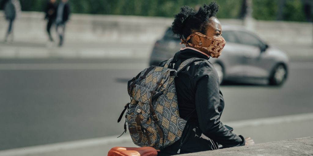 A photo of a woman in a face mask walking her bike on the street.